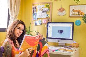 Foto de Anna Terra no seu escritório. No computador, a marca Anna Terra. Ela está sentada na cadeira e lendo o livro Comunicação Não Violenta. Na mesa outros livros empilhados e na parede artigos de decoração.